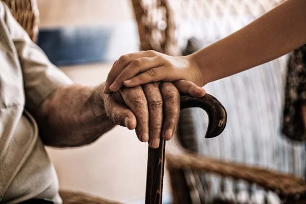 Depressed old mans hand holding for care
